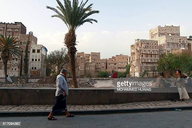 A Yemeni man walks on a street on March 23 2016 in front of UNESCOlisted buildings that were damaged by air strikes carried out by the Saudiled...
