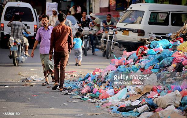 Yemeni man walks past a pile of rubbish on a main street in the third-largest city Taez on August 27, 2015. Viewed as the key to controlling the...