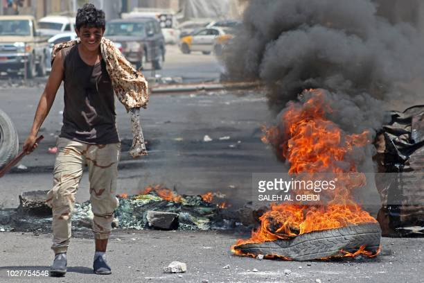 A Yemeni man walks past burning tyres in Crater on September 6 as protesters demonstrate against inflation and the rise of living costs near the...