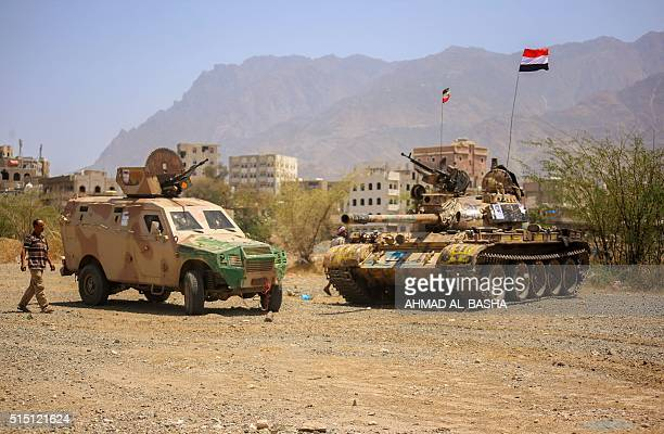 A Yemeni man walks past military vehicles at the headquarters of the army's 35th brigade in the western suburbs of Taez after forces loyal to Yemen's...