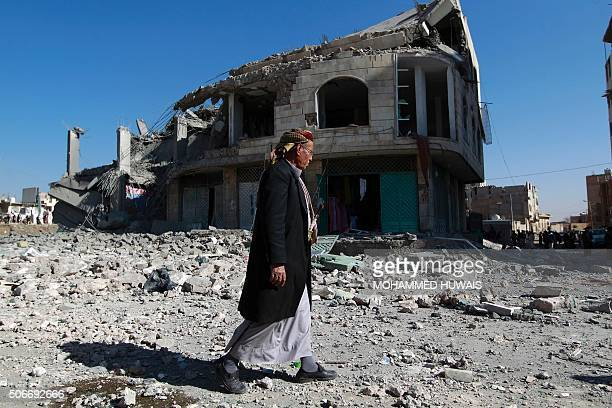 A Yemeni man walks past the site of a Saudiled airstrike that targeted a building in the Yemeni capital Sanaa on January 25 2016 A Saudiled coalition...