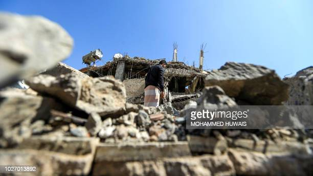 Yemeni man walks through the rubble of a building that was reportedly destroyed in Saudiled coalition air strike in the capital Sanaa on September 5...