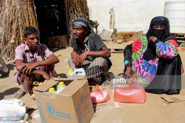 A Yemeni man woman and youth sit next to food supplies distributed by a local charity at a camp for the displaced in the northern province of Hajjah...