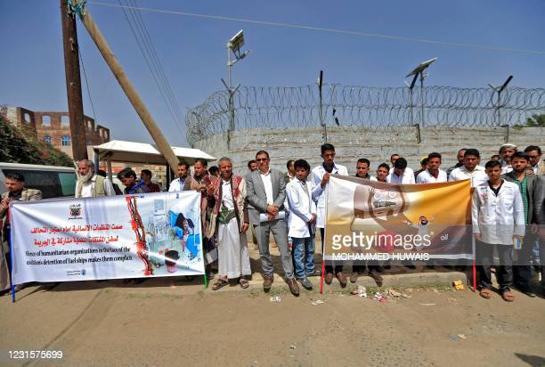 Yemeni medical staff hold banners during a demonstration outside the United Nations office in the capital Sanaa, on March 7 protesting fuel shortages...