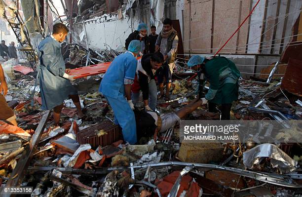 Yemeni medics and rescue workers pull out a body from the rubble of a destroyed funeral hall following reported airstrikes by Saudiled coalition...