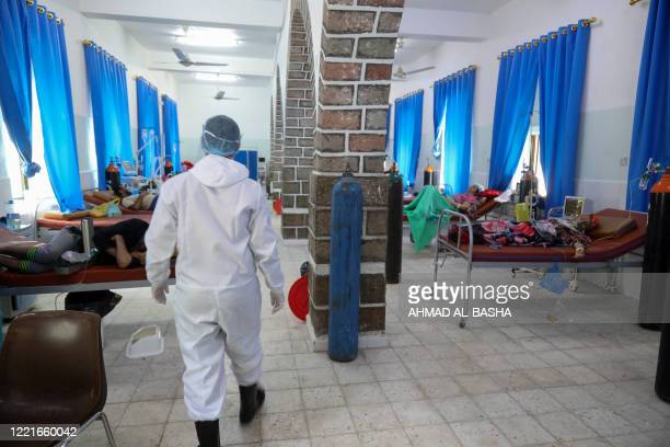 Yemeni member of the medical staff in a full hazmat suit walks in the patient ward at a quarantine center where COVID-19 patients are treated in...