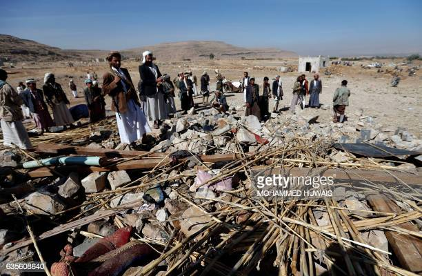 Yemeni men check the site of an air raid that hit a funeral reception in the Arhab district 40 kilometres north of the capital Sanaa on February 16...