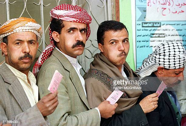 Yemeni men chew qat a popular narcotic drug as they stand in line with their voter registration cards at a polling center in Sanaa 23 September...