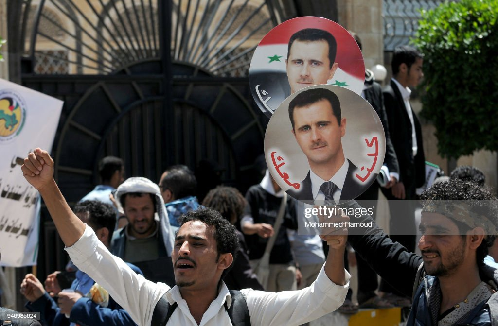 Yemeni men hold photos of Syrian President Bashar al-Assad during a protest against U.S. allied missile strikes against Syria outside the Syrian embassy on April 16, 2018 in Sana'a, Yemen. The U.S., Great Britain and France launched missile strikes in response to the Syrian goverment using chemical weapons against its own population.