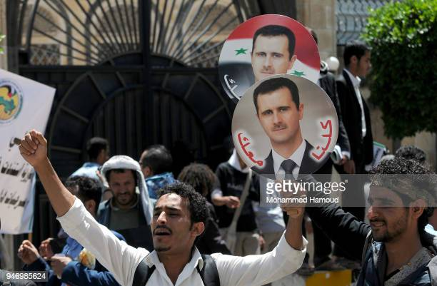 Yemeni men hold photos of Syrian President Bashar alAssad during a protest against US allied missile strikes against Syria outside the Syrian embassy...