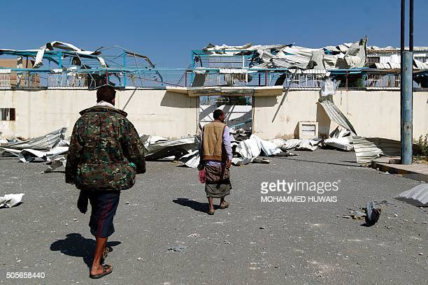 Yemeni men inspect the damage at a sports hall that was partially destroyed by Saudiled air strikes in the Yemeni capital Sanaa on January 19 2016 /...