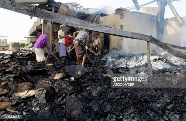 Yemeni men inspect the damages at a factory allegedly targeted by Saudiled coalition's airstrikes in the Red Sea town of Hodeidah on July 27 2018