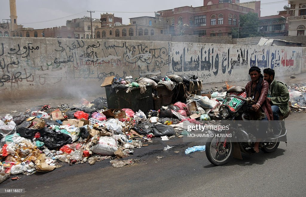 Yemeni men on a motorcycle ride past a pile of rubbish on a