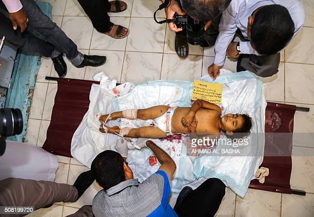 Yemeni men prepare the body of a child for burial while others take photos following a mortar shell attack on the country's flashpoint southern city...