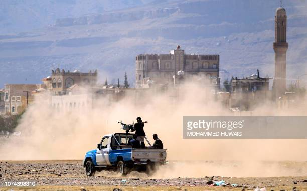 TOPSHOT Yemeni men stand at the back of an armed pick up as poeple in the capital Sanaa to show their support to the Shiite Huthi movement against...