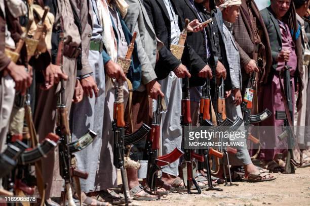 TOPSHOT Yemeni men stand with Kalashikov assault rifles during a tribal meeting in the Huthi rebelheld capital Sanaa on September 21 as tribesmen...