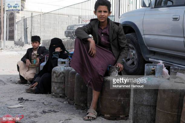 Yemeni men wait by their empty cooking gas cylinders for cooking gas supplies during a severe gas crisis, at a gas supplying station on March 05,...