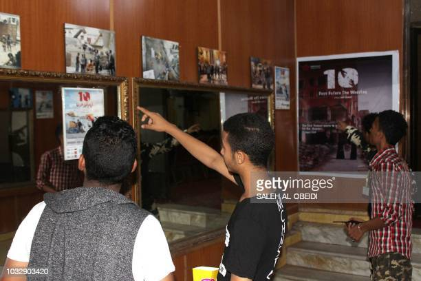 Yemeni men wath movie posters prior to the screening of the movie '10 Days Before the Wedding' at a cinema of the Southern city of Aden on September...