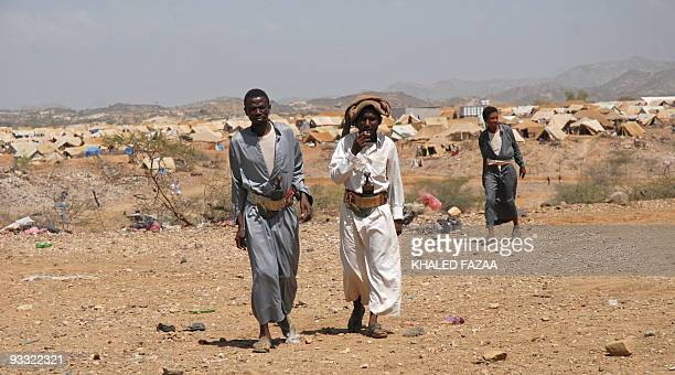 Yemeni men wearing their traditional curved daggers in their belts walk in the grounds of the Mazraq camp setup for internally displaced Yemenis in...