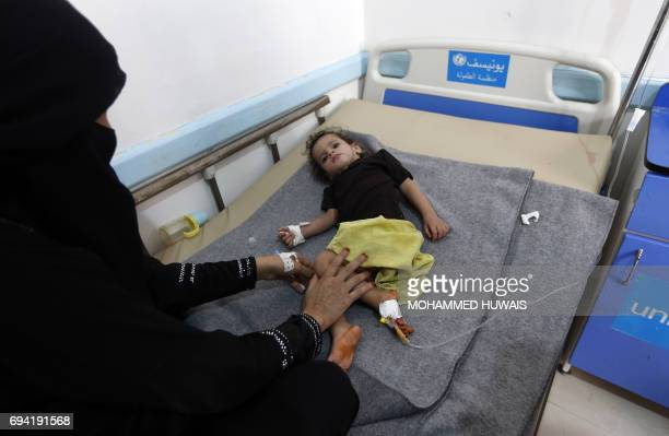 A Yemeni mother sits next to her child suspected of being infected with cholera at a makeshift hospital in Sanaa on June 9 2017 Yemen is descending...