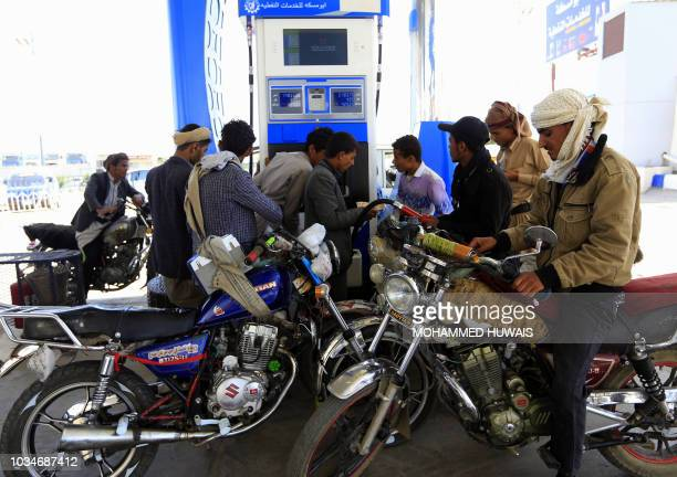 Yemeni motorcyclists fill their tanks at a petrol station amid fuel shortages in the capital Sanaa on September 17 2018 Saudi Arabia and its allies...