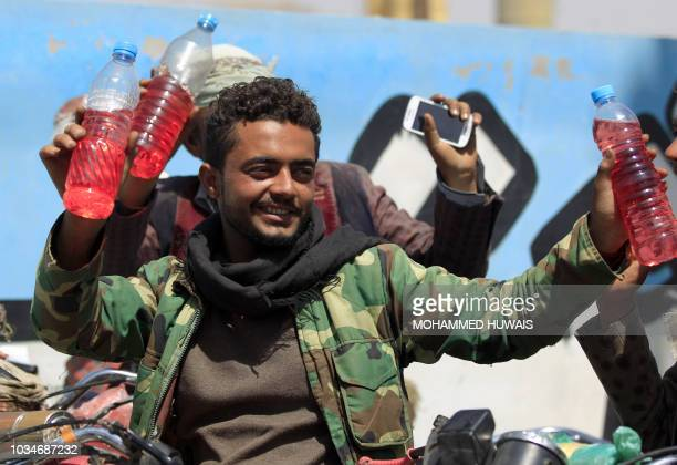Yemeni motorcyclists show fuel bottles after buying them from a petrol station amid fuel shortages in the capital Sanaa on September 17 2018 Saudi...