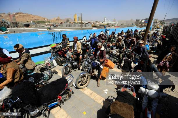 Yemeni motorcyclists wait in line to buy fuel at a petrol station amid fuel shortages in the capital Sanaa on September 17 2018 Saudi Arabia and its...
