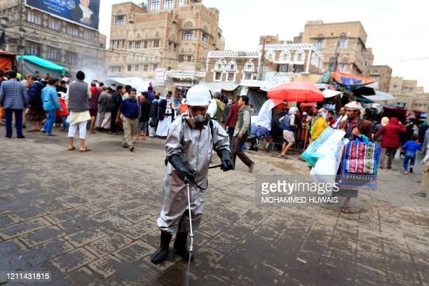 Yemeni municipal worker sprays disinfectant liquid as a measure against the novel coronavirus in the old city market of the capital Sanaa on April 30...
