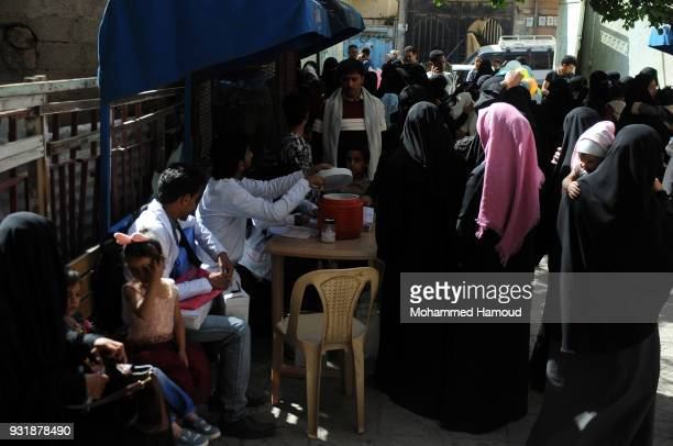 Yemeni people attend a health center to give their children vaccine against diphtheria disease at a health center on March 13 2018 in Sana'a Yemen...