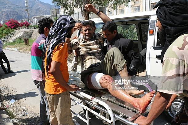 Yemeni people carry an injured man after Saudiled coalition airstrikes targeting Houthicontrolled areas in Taiz's Su'bat region on October 25 2015