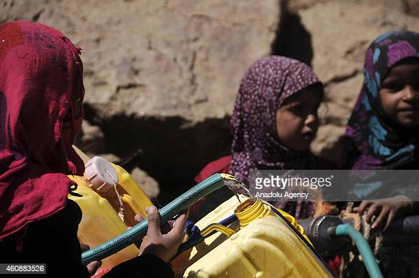 Yemeni people carry containers to fill water from a public tap in Kavala area of Yemen on December 28 2014 Ibb faces water crisis as Yemen is one of...