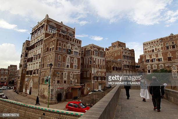 Yemeni People cross a bridge leading to UNESCOlisted buildings in the old city of the Yemeni capital Sanaa following heavy rainfall on April 12 2016...