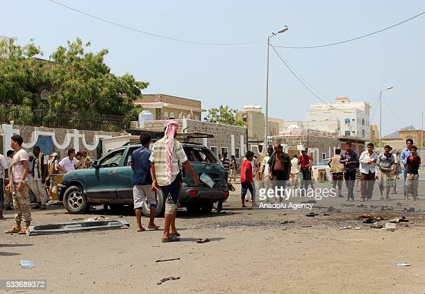 Yemeni people inspect an incident area after a car bomb attack in Aden Yemen on May 23 2016 At least 30 civilians killed and 35 others were wounded...