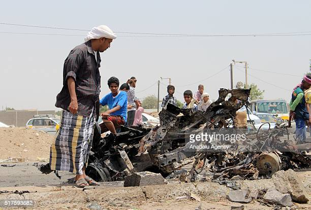 Yemeni people inspect an incident area after car bomb attack carried out near AlBuraiqeh check point in Aden Yemen on March 26 2016