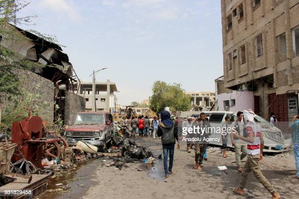 Yemeni people inspect wreckages after a boobytrapped car hit a mess hall serving Yemeni forces trained by the United Arab Emirates in Sheikh Othman...