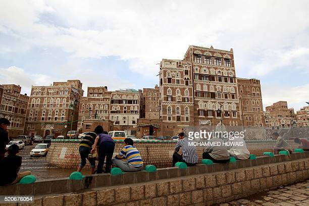 Yemeni People sit opposite UNESCOlisted buildings in the old city of the Yemeni capital Sanaa following heavy rainfall on April 12 2016 / AFP /...
