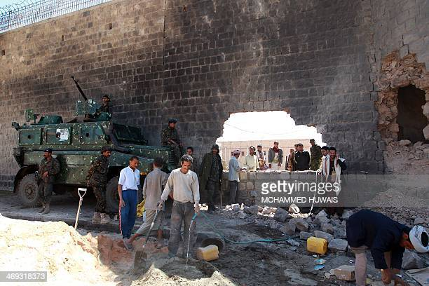 Yemeni policemen stand guard as workers repair the central prison's outer wall on February 14 2014 in the capital Sanaa a day after a deadly assault...