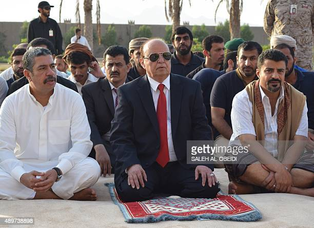 Yemeni President Abedrabbo Mansour Hadi sits next to Prime Minister Khaled Bahah as they perform prayers for the Muslim holiday of Eid alAdha in the...
