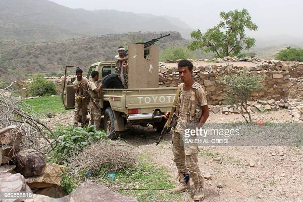 Yemeni pro-government fighter poses in front of an armed pick-up as Emirati supported forces take over Huthi bases on the frontline of Kirsh between...