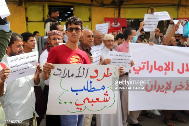 """Yemeni protester holds a sign reading in Arabic """"evicting the Emirates is a national demand"""", during a demonstration against the United Arab Emirates..."""