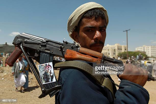 A Yemeni protester holds a weapon bearing a portrait of Ahmed Ali Abdullah Saleh the son of Yemen's former president Ali Abdullah Saleh who stepped...