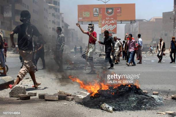 Yemeni protesters block a road as they protest against inflation and the rise of living costs in the country's second city of Aden which is held by...