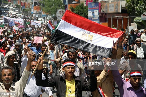 Yemeni protesters one waving an Egyptian national flag flash the sign of victory during a demonstration in the strategic city of Taez on March 28 in...