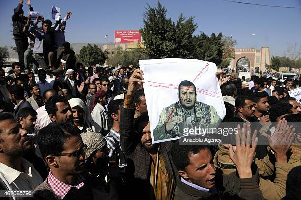 Yemeni protestors gather at Change Square shout slogans and hold a poster of leader of Houtis Sheikh Sayyid AbdulMalik with a crossed sign on it...