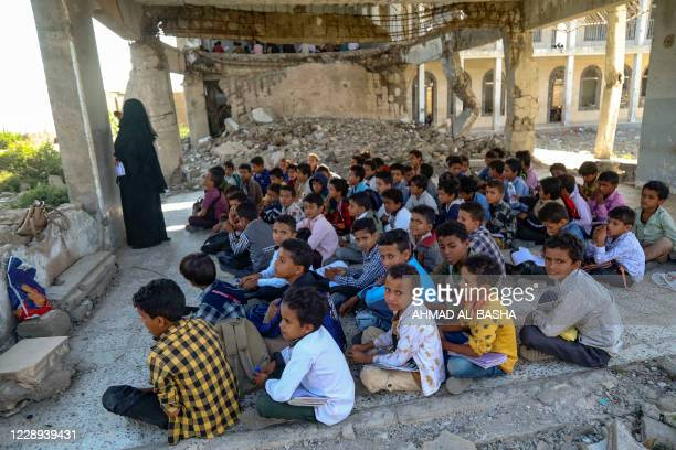 Yemeni pupils attend class on the first day of the new academic year in a makeshift classroom in their school compound, which was heavily damaged in...