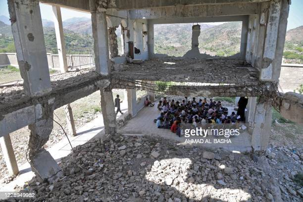 Yemeni pupils attend class on the first day of the new academic year, in a makeshift classroom in their school compound which was heavily damaged in...