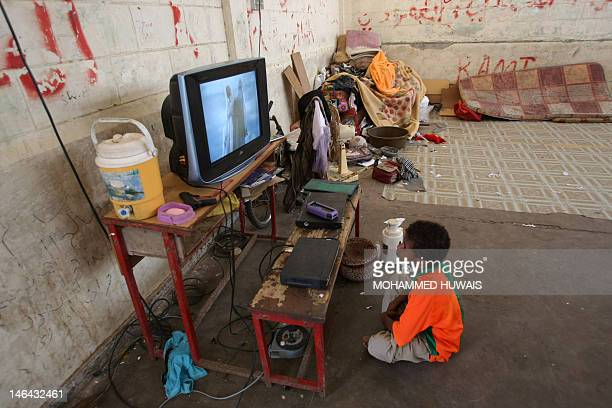 A Yemeni refugee child sits watching TV in the grounds of a public school in the port city of Aden on June 16 now being used as the living quarters...