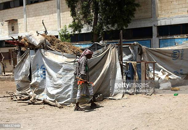 A Yemeni refugee man walks past a shelter buildt in the grounds of a public school in the port city of Aden on June 16 now being used as the living...