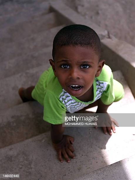 A Yemeni refugee toddler crawls up a set of stairs in the grounds of a public school in the port city of Aden on June 16 now being used as the living...
