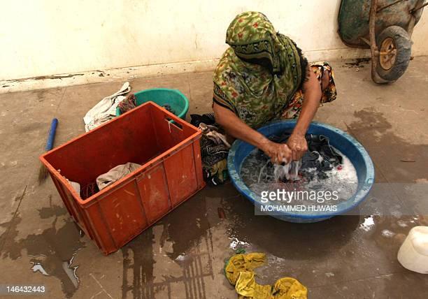 A Yemeni refugee woman washes clothes in the grounds of a public school in the port city of Aden on June 16 now being used as the living quarters for...